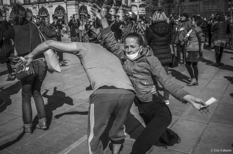 Photo noire et blanche de Danseurs masqués dans la rue